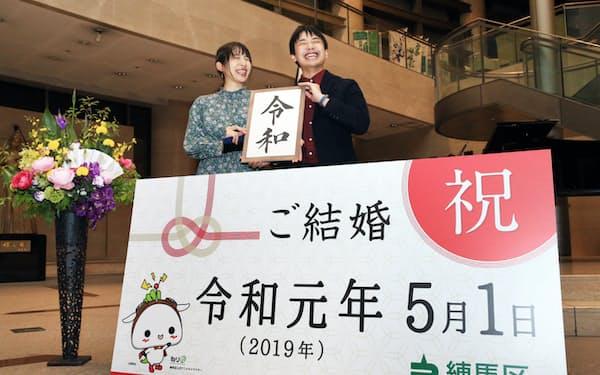 令和改元後、一番乗りで区役所に婚姻届を出し記念撮影するカップル(1日、東京都練馬区)=横沢太郎撮影
