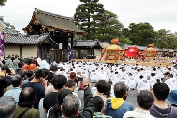 京都御苑内を巡行する御霊神社のみこし。左は京都御所(1日、京都市上京区)=小川望撮影