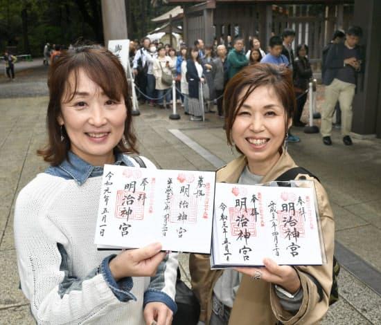 「令和元年」の日付が入った明治神宮の御朱印を手にする人たち(1日、東京都渋谷区)