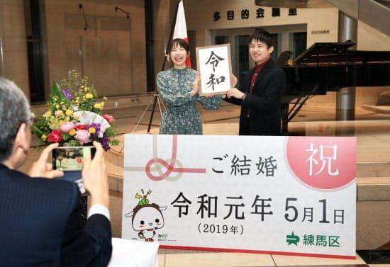 令和改元の日に一番乗りで練馬区役所に婚姻届を出し、記念写真を撮るカップル(1日、東京都練馬区)