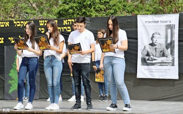2日、イスラエル中部ベイトシェメシュで開かれた、「命のビザ」の杉原千畝を顕彰する式典。杉原の写真が掲げられた=共同
