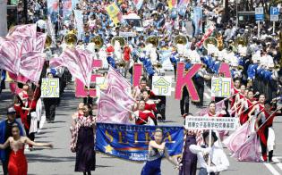 「博多どんたく港まつり」で、令和と書かれたプラカードを掲げて行進する精華女子高校の吹奏楽部(3日、福岡市)