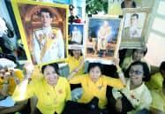 タイのワチラロンコン国王の戴冠式を祝い、王宮前で肖像画を掲げる人たち(4日午前、バンコク)=三村幸作撮影