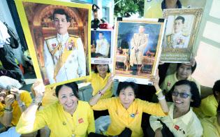タイのワチラロンコン国王の戴冠式を祝い、王宮前で肖像画を掲げる人たち(5月4日午前、バンコク)=三村幸作撮影