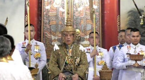 王冠をかぶり玉座につくワチラロンコン国王(中)(4日、バンコク)=タイ政府配信の映像から