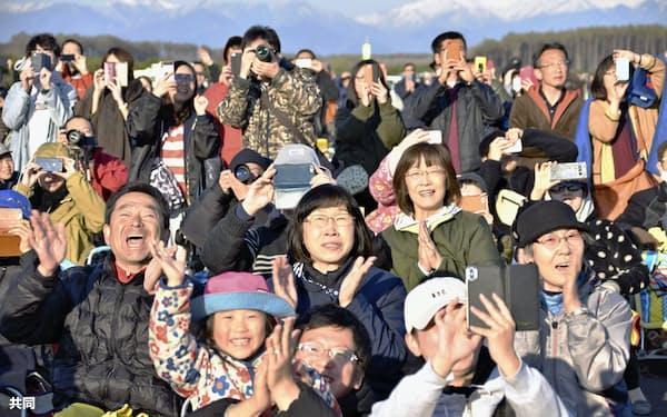 ロケットの打ち上げに歓声を上げる町民ら=共同