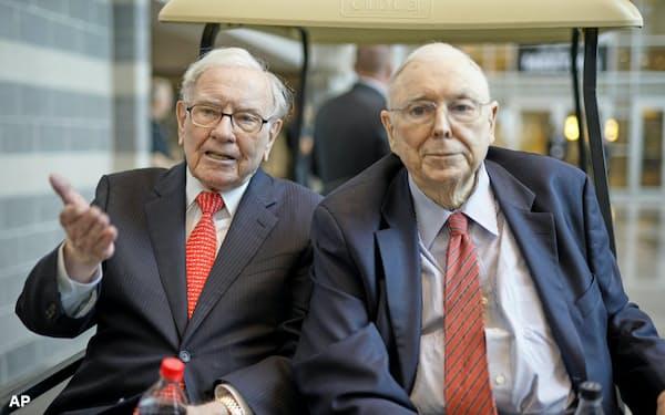 株主総会会場で記者団の質問に答えるバフェット氏(左)=AP