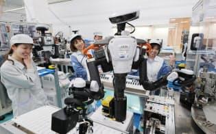 カメラが搭載された「目」と左右にある2本の「腕」が人間のような作業を可能にするロボット。「今日は機嫌がいいね」と従業員に囲まれる(長野県駒ケ根市のコガネイ駒ケ根事業所)=山本博文撮影
