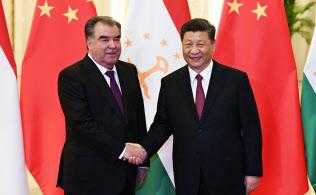 タジキスタンのラフモン大統領と握手する中国の習近平主席。タジキスタンは返済の代わりに土地と鉱物資源を中国に提供したとされる=AP