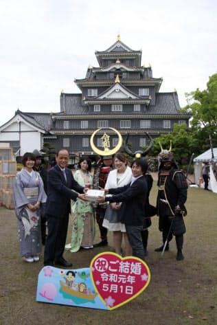 婚姻届を提出した1組目に記念品を手渡す岡山市の大森市長(左から2人目)=1日、岡山市