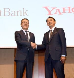 ヤフーを連結子会社化すると発表し、握手するソフトバンクの宮内謙社長(左)とヤフーの川辺健太郎社長(8日、東京都港区)