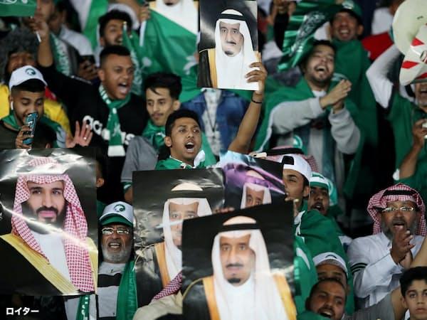 サッカーの国際試合でサルマン国王やムハンマド皇太子の写真を掲げるサウジのサポーター=ロイター