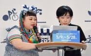 東京五輪観戦チケット抽選販売の申込受付が始まり、手続きのデモンストレーションをするお笑いタレントの渡辺直美さん(左)(9日、東京都港区)