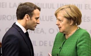 マクロン仏大統領(左)とメルケル独首相の次期EUトップを巡る駆け引きが本格化=AP