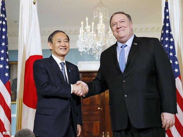 会談前にポンペオ国務長官(右)と握手する菅官房長官(9日、米ワシントンの国務省)=共同