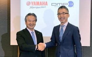 資本業務提携を発表するヤマハ発動機の藤田宏昭上席執行役員(左)とDMPの山本達夫社長(10日、東京・千代田)