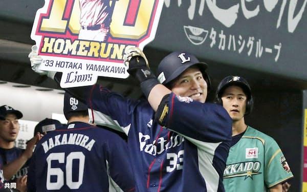 3回、通算100本塁打を放ち、記念のボードを掲げる西武・山川(12日、札幌ドーム)=共同