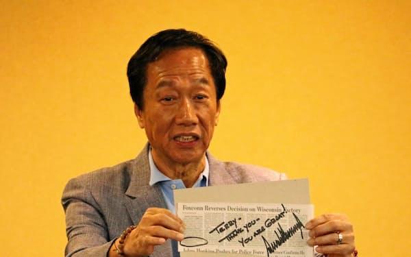 鴻海の郭氏はトランプ氏から会談の際にもらったサインを掲げ、関係をアピールした(6日、台北市内)