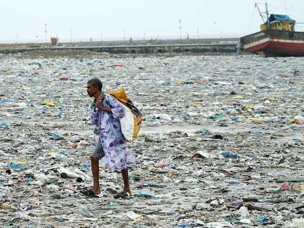 海岸に打ち上げられたプラスチックごみを集める男性(2018年7月、インド・ムンバイ近郊)