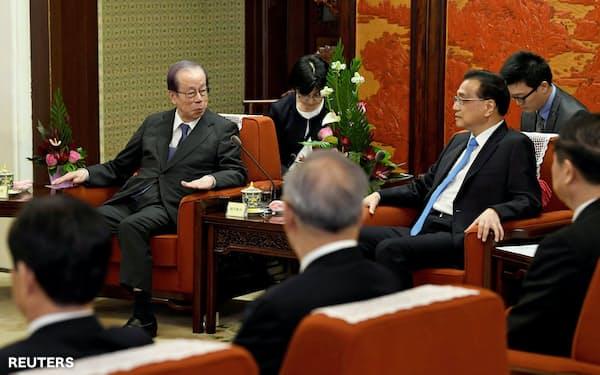 2018年10月10日、北京市で中国の李克強首相(右から3番目)と会談する福田康夫元首相(左から2番目)(左)=ロイター