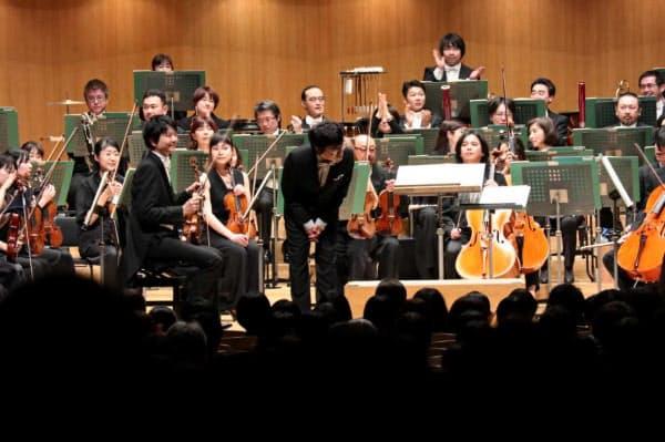 京都市交響楽団による「交響曲第2番」の演奏を見届け、聴衆にあいさつする岸田繁(中央、3月30日、東京・初台の東京オペラシティ)=京響提供
