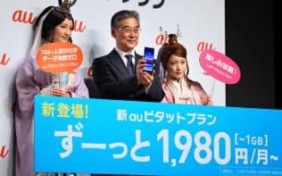 新しい料金プランを発表するKDDIの東海林取締役(中)ら(13日午前、東京都港区)