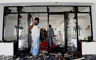 13日、襲撃されたモスク内を歩くイスラム教徒の男性(スリランカ北西部)=ロイター