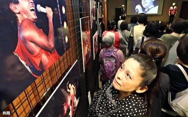 昨年5月に亡くなった歌手、西城秀樹さんの写真パネルやミュージックビデオを見る来場者(14日午前、東京・銀座)=共同