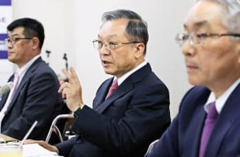 西日本FHの谷川社長(中)は記者会見で長引く低金利政策に厳しい表情をみせた(14日、福岡市中央区)