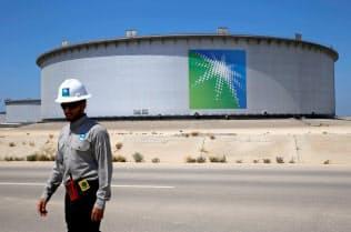 サウジアラビア国営石油会社、サウジアラムコの貯蔵タンクの近くを歩く従業員(2018年5月、サウジ国内の石油精製施設)=ロイター