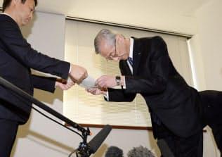 国交省の鶴田浩久東京航空局長(左)から業務改善命令の文書を受け取るIHIの満岡次郎社長(4月9日、東京都千代田区)