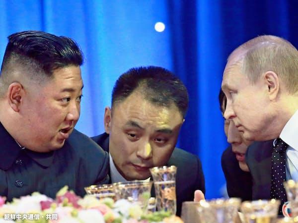 夕食会でロシアのプーチン大統領(右)と話す北朝鮮の金正恩委員長(4月25日、ロシア・ウラジオストク)=朝鮮中央通信・共同
