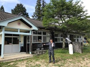 工場に再生した廃校を前に構想を巡らす高橋社長
