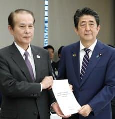 教育再生実行会議の鎌田座長(左)から提言書を受け取る安倍首相(17日、首相官邸)