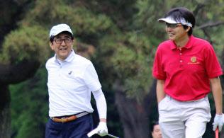 プレー中に笑顔をみせる安倍首相(左)(18日午前、神奈川県茅ケ崎市)