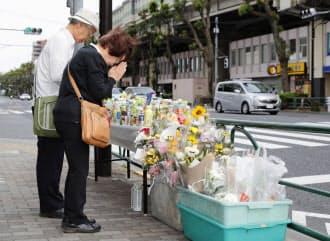 東京・池袋で乗用車が暴走し母子が死亡した事故の現場で手を合わせる人たち(18日午後)=共同