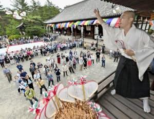 唐招提寺の「うちわまき」で鼓楼からうちわ「宝扇」をまく僧侶(19日午後、奈良市)=共同