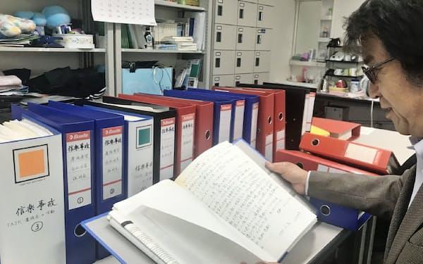 信楽高原鉄道事故の遺族が残した資料を眺める関西大の安部教授(17日、大阪府高槻市)