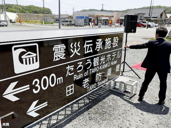 岩手県宮古市田老地区で披露された「震災伝承施設」を示すマークを用いた案内標識。左奥は田老防潮堤(20日午前)=共同