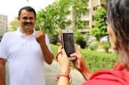 投票済みを示すインクの付いた指を撮影し知人に送る有権者(12日、北部ハリヤナ州)
