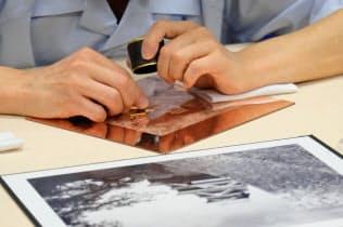 金属板に熊本城を彫る国立印刷局東京工場の彫刻師(17日、東京都北区)