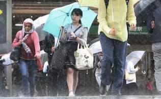 強い雨が降る中、傘を差して歩く人たち(21日午前、JR新宿駅前)