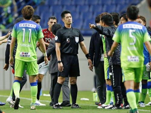 17日のJ1浦和―湘南戦で、湘南のゴールを得点と認めず選手らの抗議を受ける山本雄大主審=中央(埼玉スタジアム)=共同