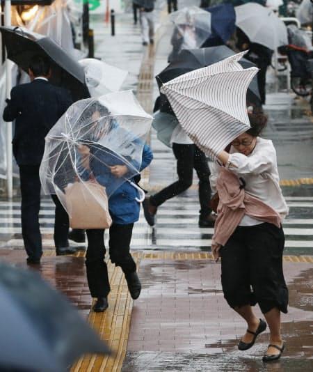 強い風雨の中、傘を差して歩く人たち(21日、東京都新宿区)