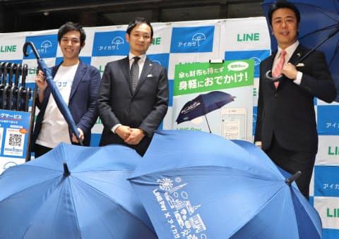 傘のシェアサービスで会見するLINE Fukuokaの鈴木COO(中)ら(21日、福岡市)