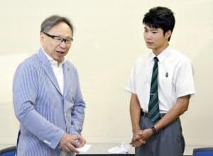 猪野屋博さん(左)と再会し、飛行機代のお礼をする崎元颯馬さん(21日、那覇市)=共同