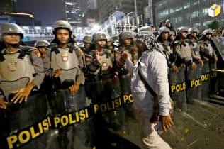 21日、ジャカルタ中心部の総選挙監視庁前を警備する治安部隊=ロイター
