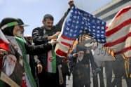米国の国旗に火を付けるイランの民衆(10日、テヘラン)=AP