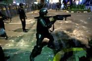 22日、ジャカルタ中心部で催涙弾を発射する治安部隊=ロイター