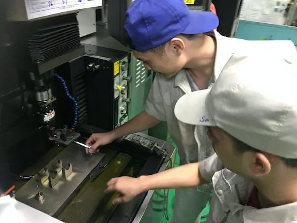 日本で技術を学んだベトナム人が放電を使って形を整える加工を別のベトナム人に教える(ハノイの吉中精工)